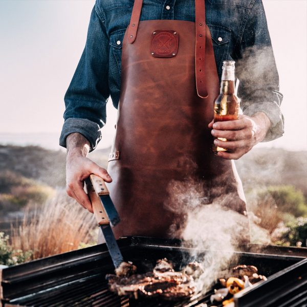 Person with a beer in his hand working the bbq while wearing his Witloft apron