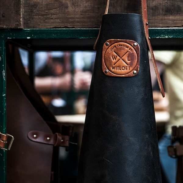 A black/cognac colored and dark brown colored apron hanging on a peg