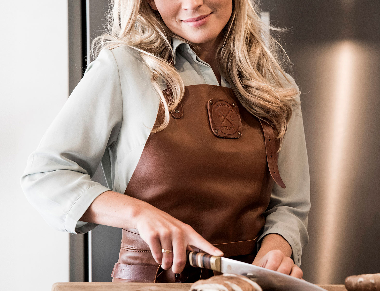 WITLOFT Cooking at home Story cutting bread wearing a Cognac Comfort Collection