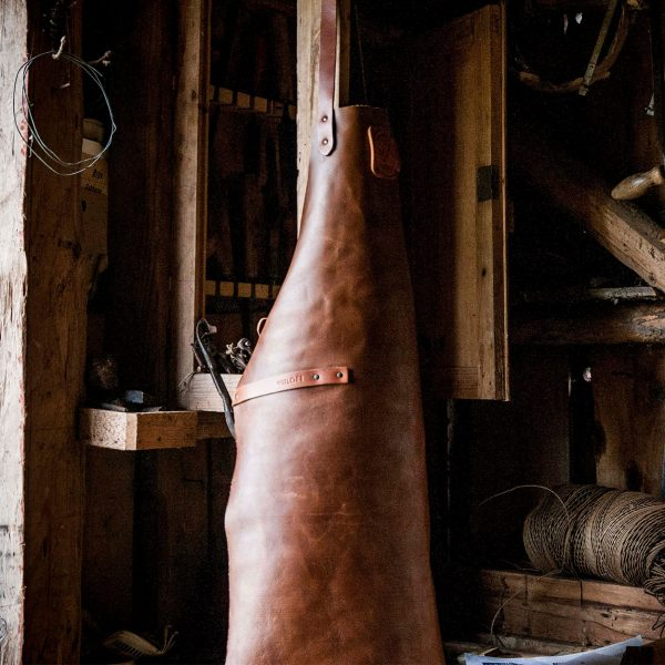 Cognac colored Witloft apron hanging in a shed on a peg